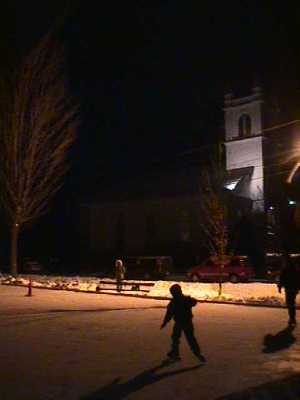 Picture of kids skating at the Lancaster, New Hampshire millenium celebration at night with the Congregational church in the background.