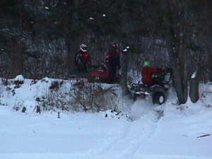 Picture of an ATV rider climbing the bank from the beaver dam up to the snowmobile trail with some folks on snowmobiles waiting to talk with them.