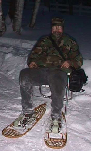 Picture of the webmaster, Ed Sanders sitting in a lawn chair getting ready to remove his snowshoes.